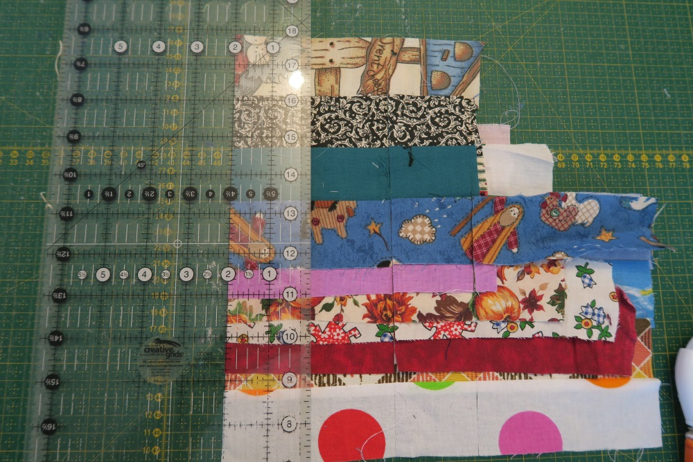 """Slide my ruler back to the left one more time and cut at 2"""". By holding my ruler there, it keeps the pieces in position better.  (If you have one of the June Taylor rulers with slots - that works well also at keeping things in place while you cut)."""
