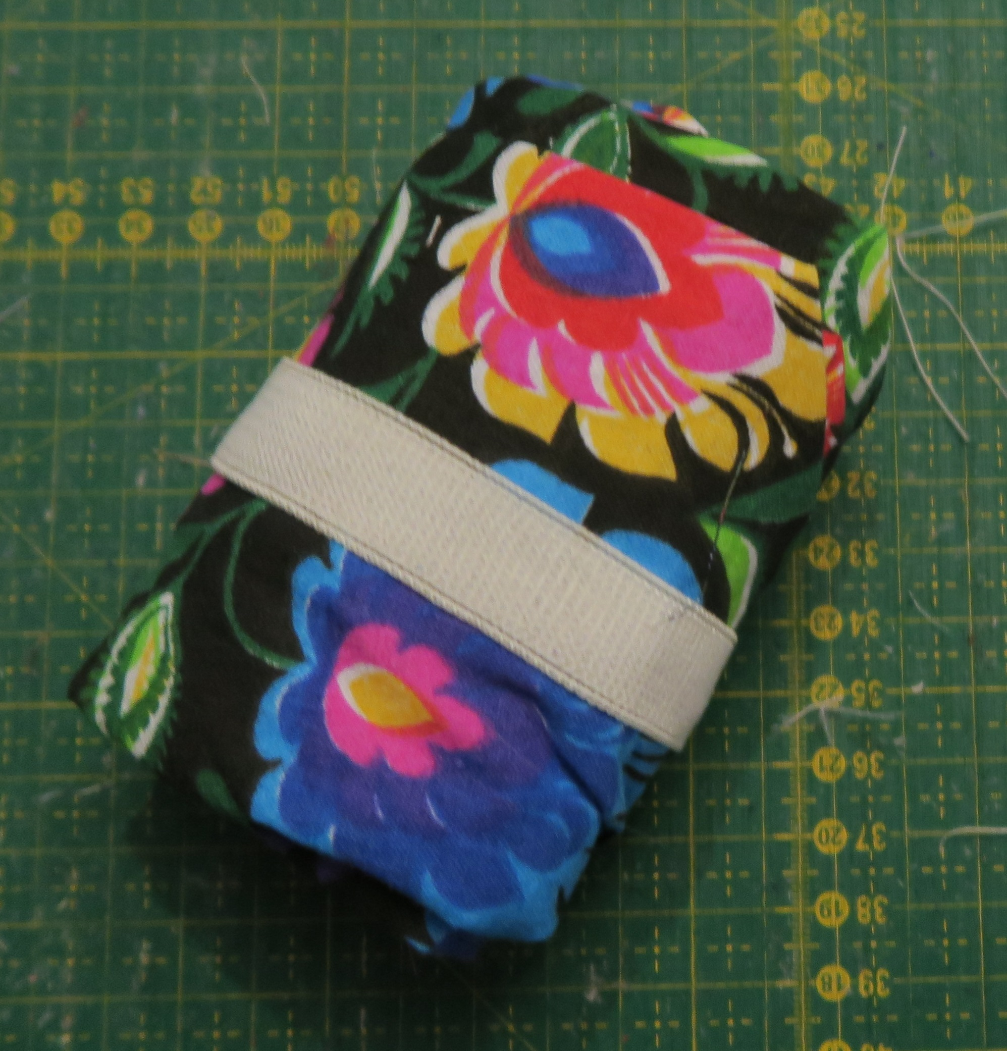 rolled up fabric, approximately 1 yard, but the size of the floral fabric is impossible to determine with the current folding. It appears to be a fabric brick.