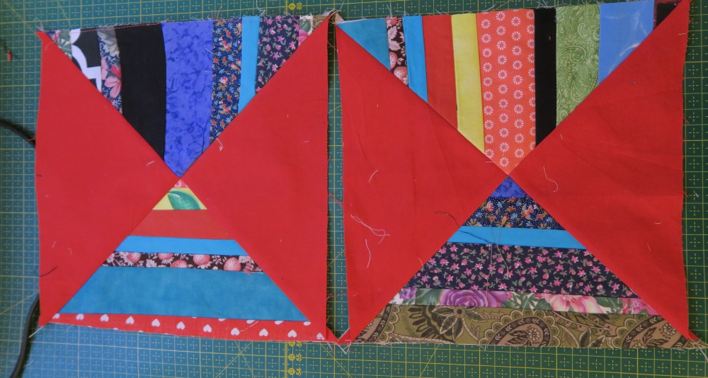 Two parallel blocks of red fabric in triangles forming squares sitting on top of a quilt cutting board. Scrap strips were sewn together to form triangles which are matched diagnally by solid red triangular fabric.