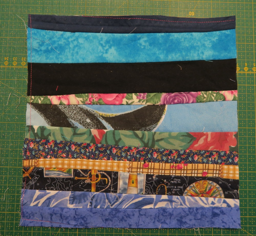 scrap fabric block on top of green quilting cutting board. Fabric strips are aligned horizontally in the following way: navyish blue fabric, skyblue and faded slightly resembling snowflakes fabric, solid black or dark brown fabric (its disputed), floral fabric with green leaves and pink and purple flowers with beige background, killer whale in water fabric strip, floral green leaves with red flowers fabric strip, fall fabric with red, blue, and green leaves and snow flakes, golden background with bird cage containing pink birds fabric, lighthouse fabric with anchor and a black and white map background with colorful compass, blue and white leafed fabric, faded blue fabric.