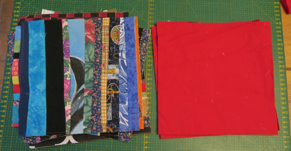 Previously mentioned fabric, stacked next to a stack of red fabric all on top of a green cutting quilting cutting board