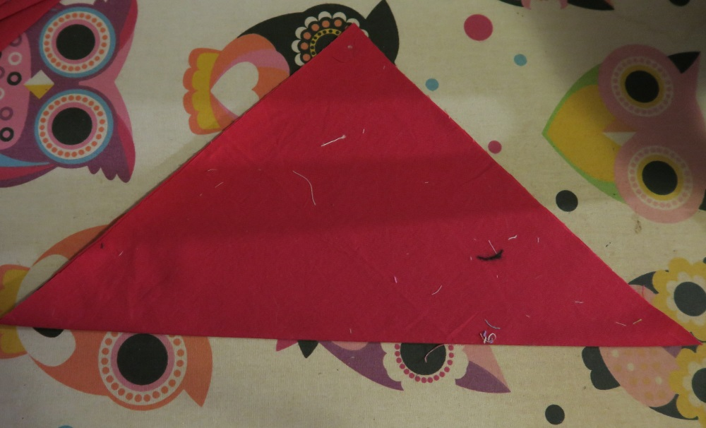 Red triangular fabric on top of colorful owl ironing board