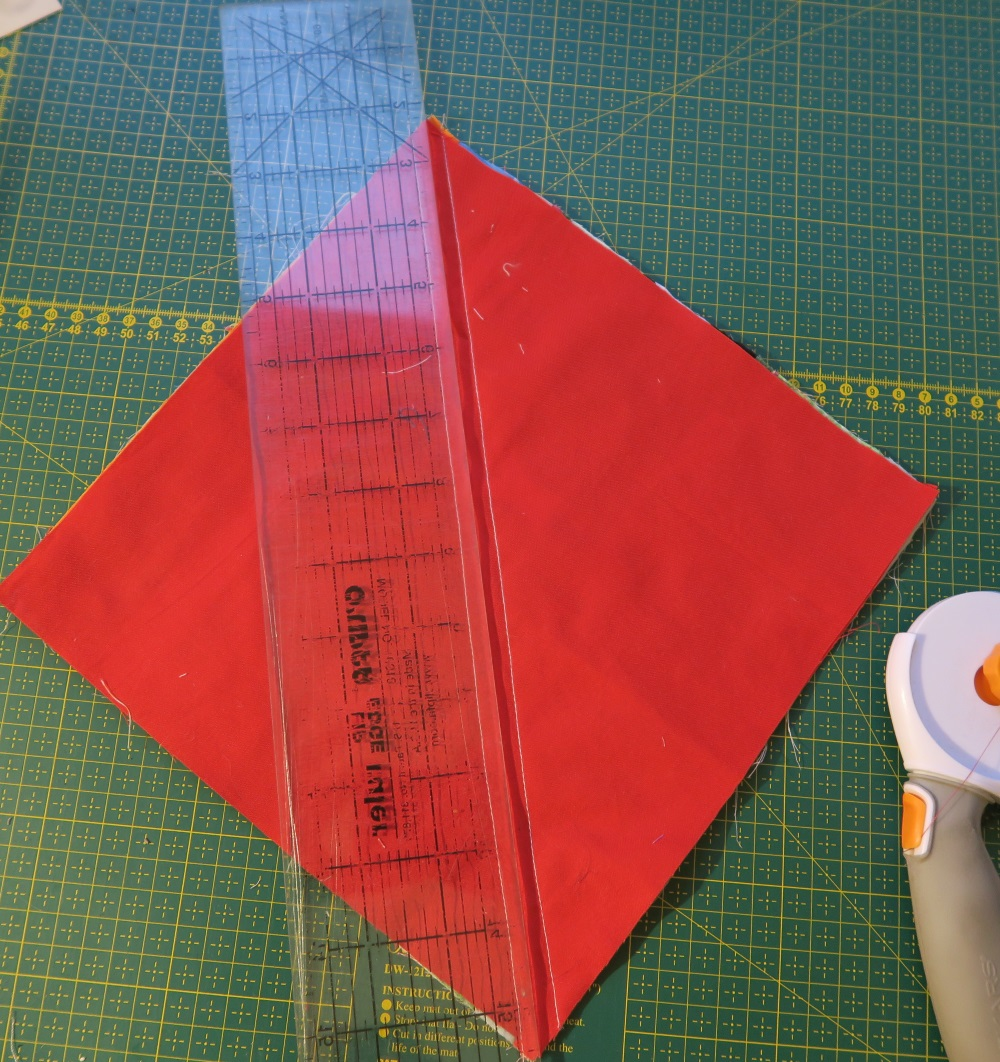 Red square of fabric on top of green quilting cutting board, with ruler placed across diagnolly and a cutter sitting next to the fabric.