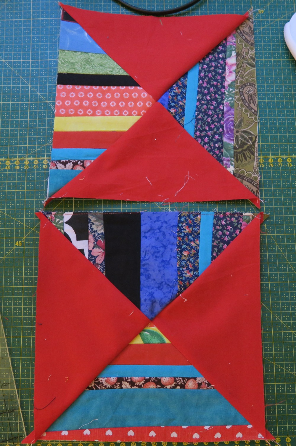 Two square blocks one position atop another on top of the green quilting cutting board red triangular half squares opposite each other revealing that the two pieces of fabric could be pasted together to reveal the lines match.