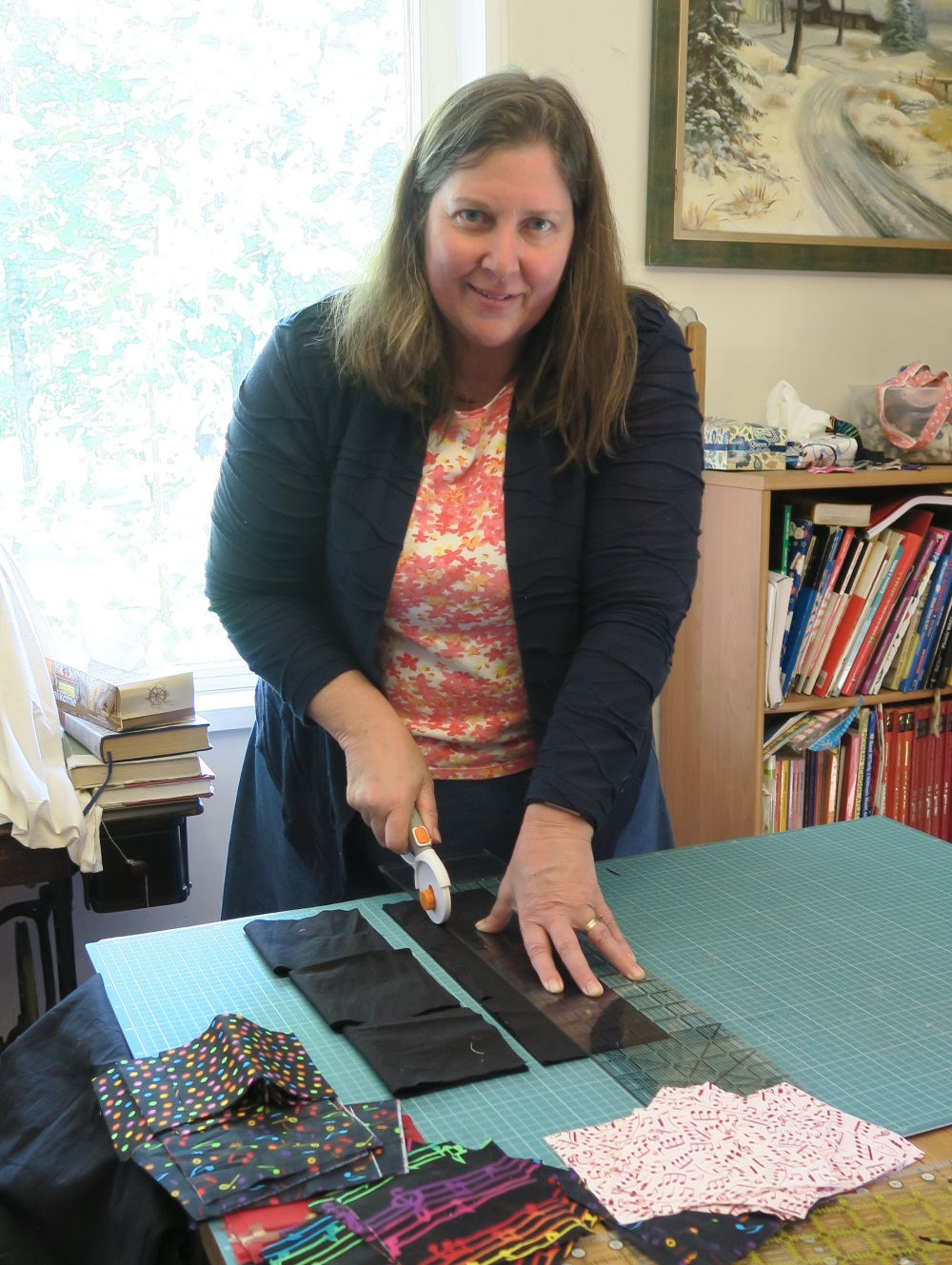 Rachael cutting black fabric on top of quilting measuring and cutting board. A painting is in the background along with a bookshelf full of quilting books. Cut musical fabric is in the foreground