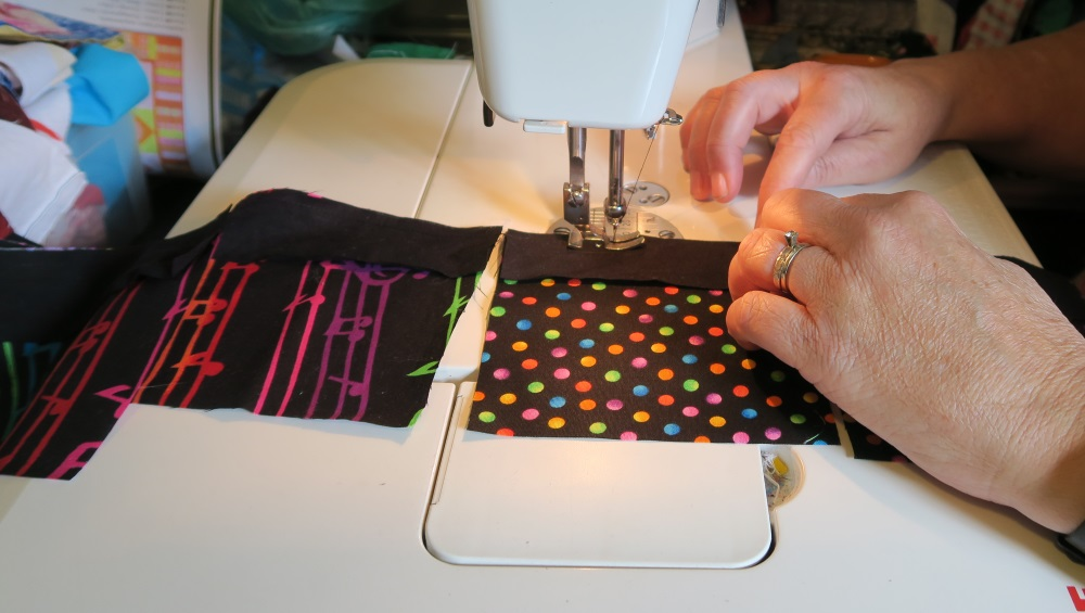 Rachael chain piecing: sewing, with a white sewing machine, the black fabric to poka-dot fabric. A previously sewn black fabric is shown sewn to the musical fabic.