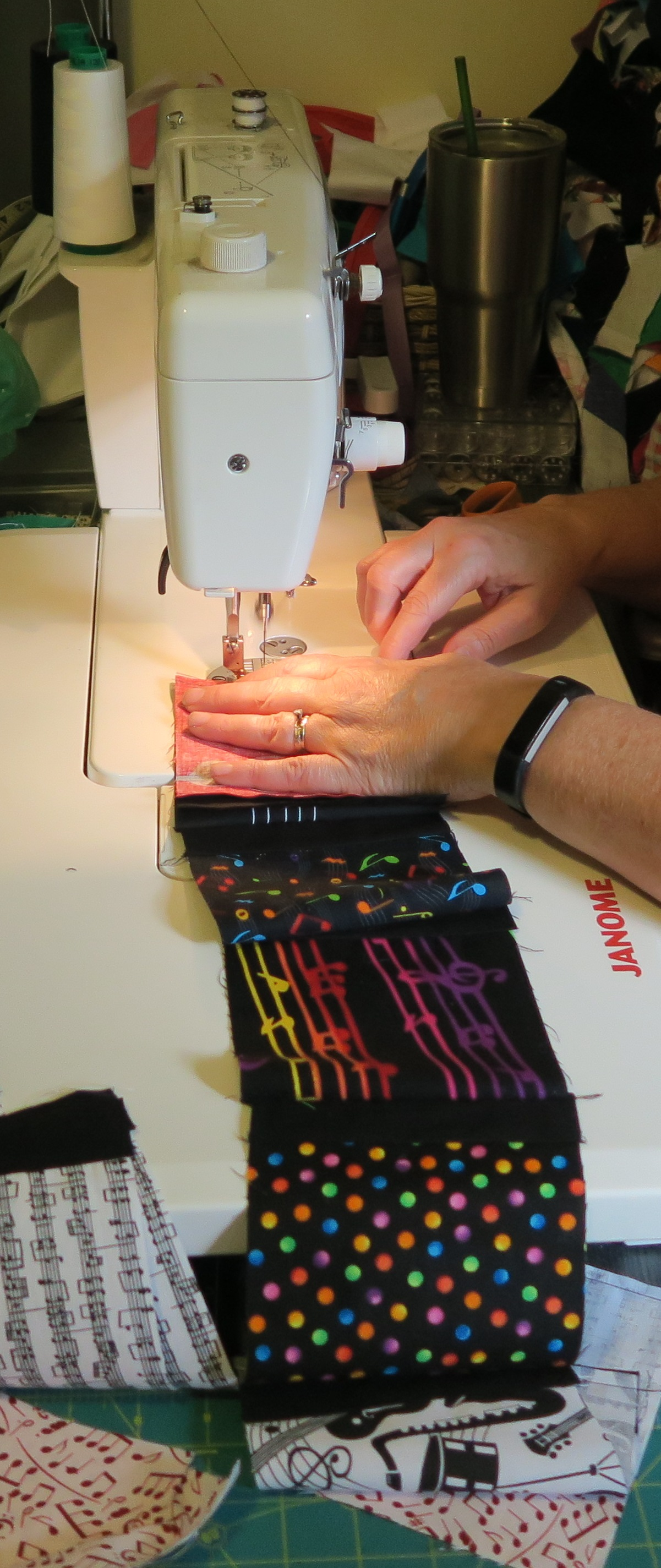 Rachael sewing the musical strips with a white sewing machine. The strip of fabric extends beyond the length of the sewing machine