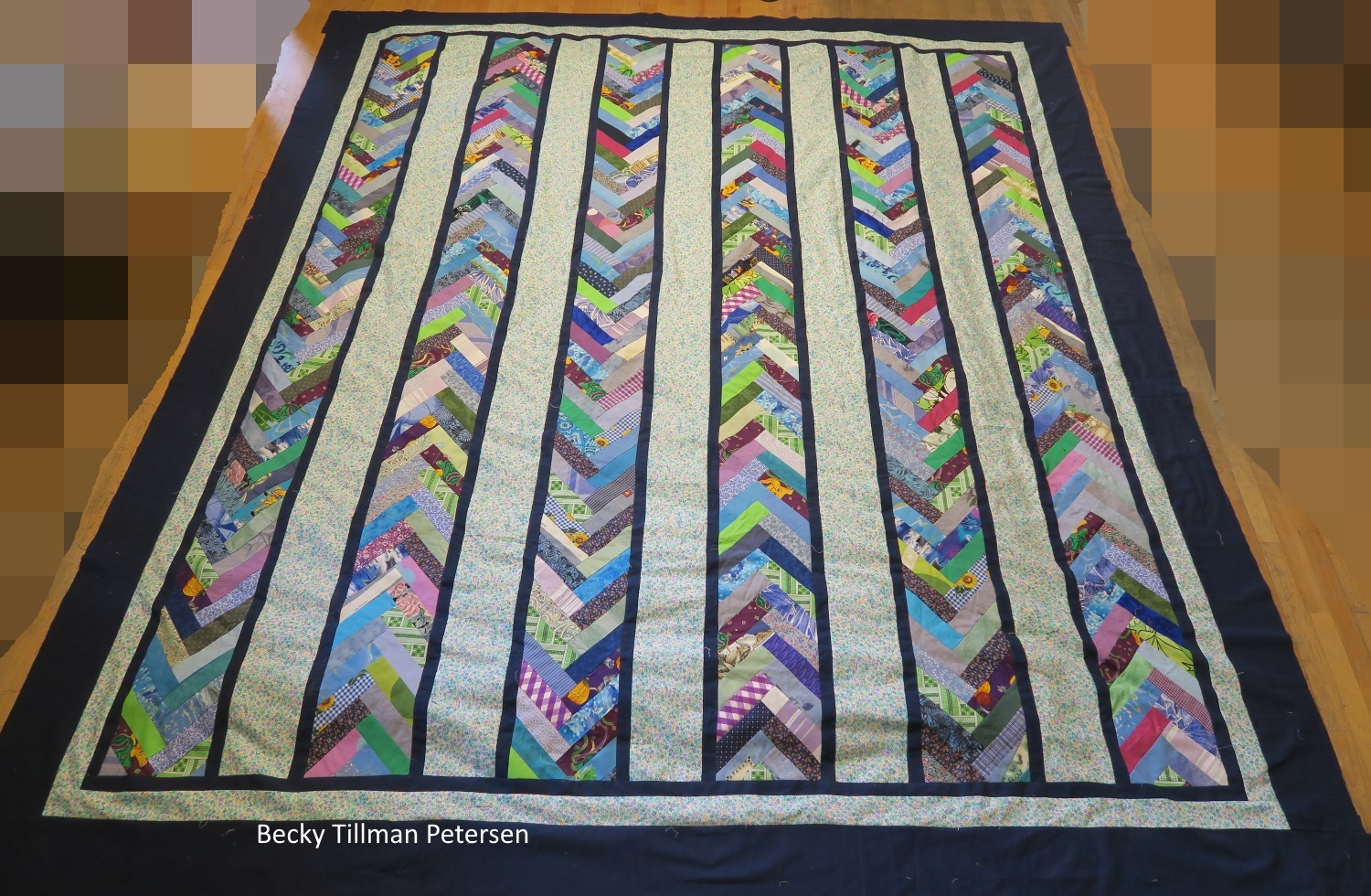 """Quilt named """"braided scraps"""" sitting on a wooden floor. The scrappy pieces are interlinked forming arrows within columns pointing alternating pointing upwards or downwards inversly according to the column preceding it. Between the scrap columns are white with blue dots columns. The exterior border is dark blue while the middle border is white with blue dots as the columns, and the interior border is dark navy blue, matching the exterior border."""