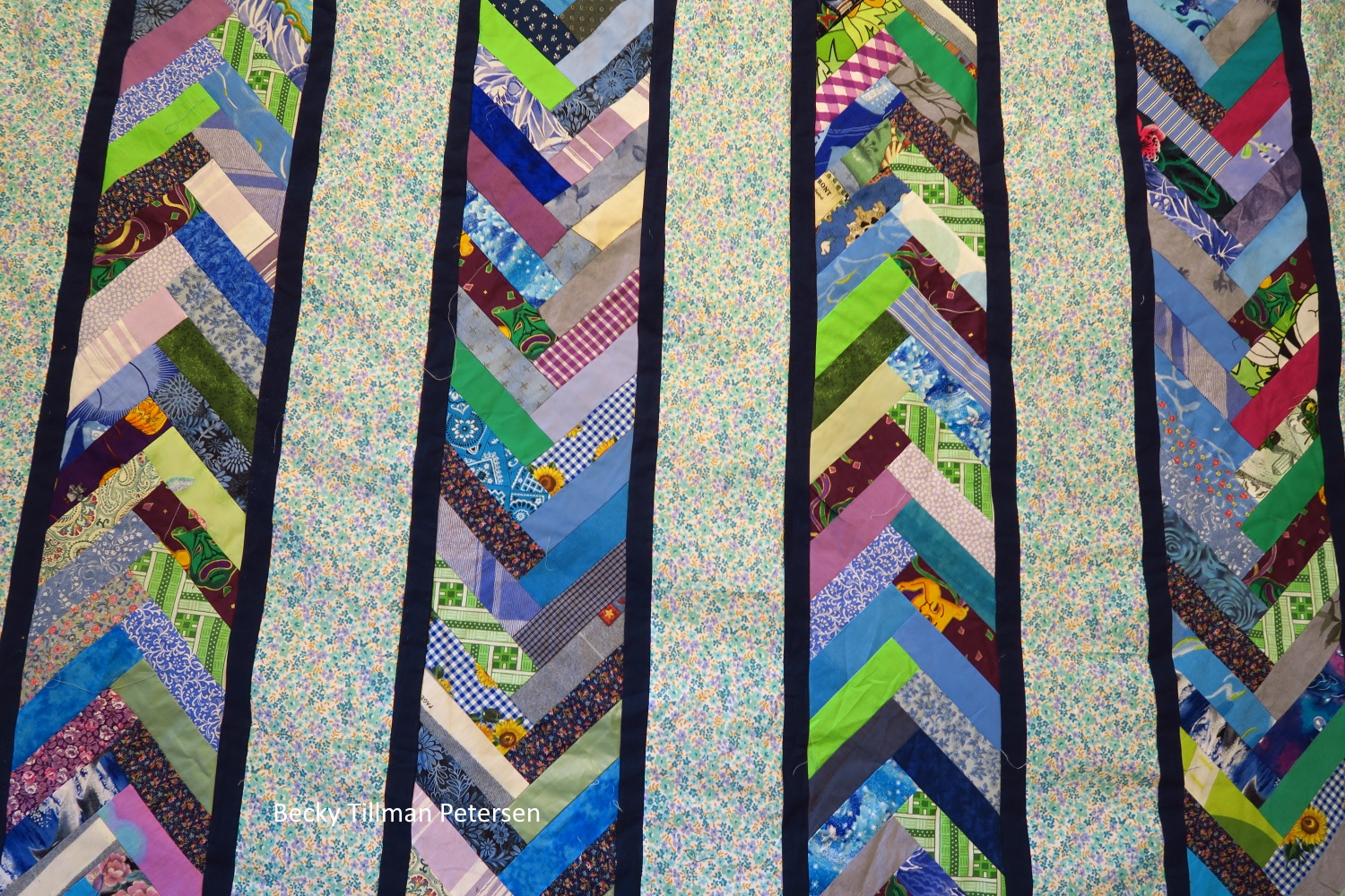close up of the patterns of the columns, which reveals a multi-color in the blue dot columns. The scraps appear rando, while maintaining the order of pointing upward or downward.
