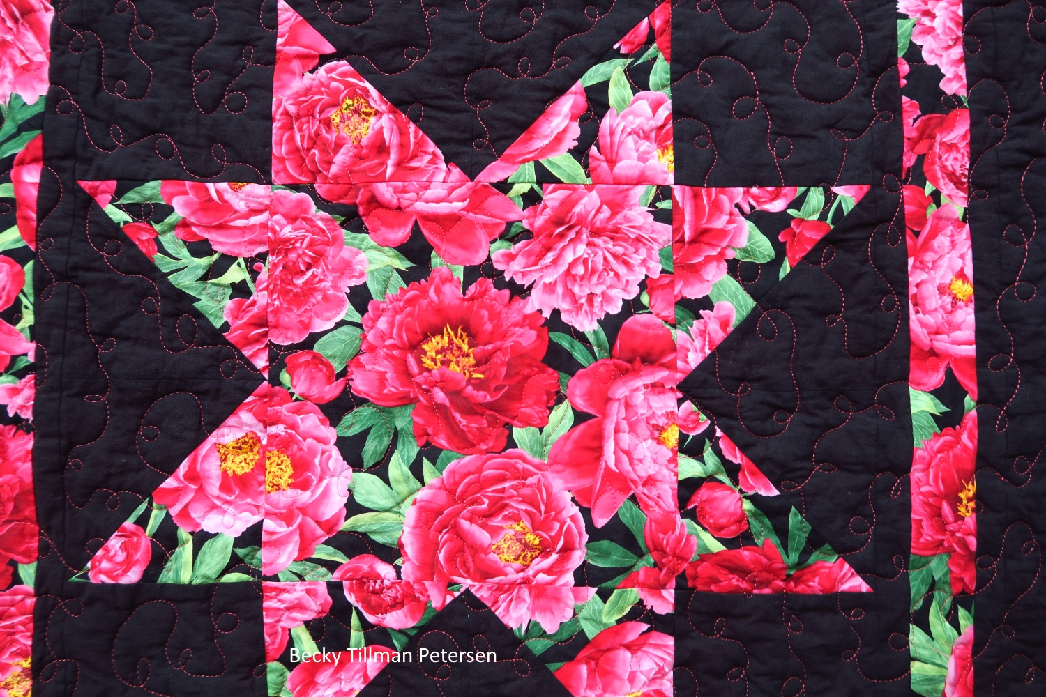close up photo of star in center of quilt. In the center of the star is a red rose with yellow golden pollen