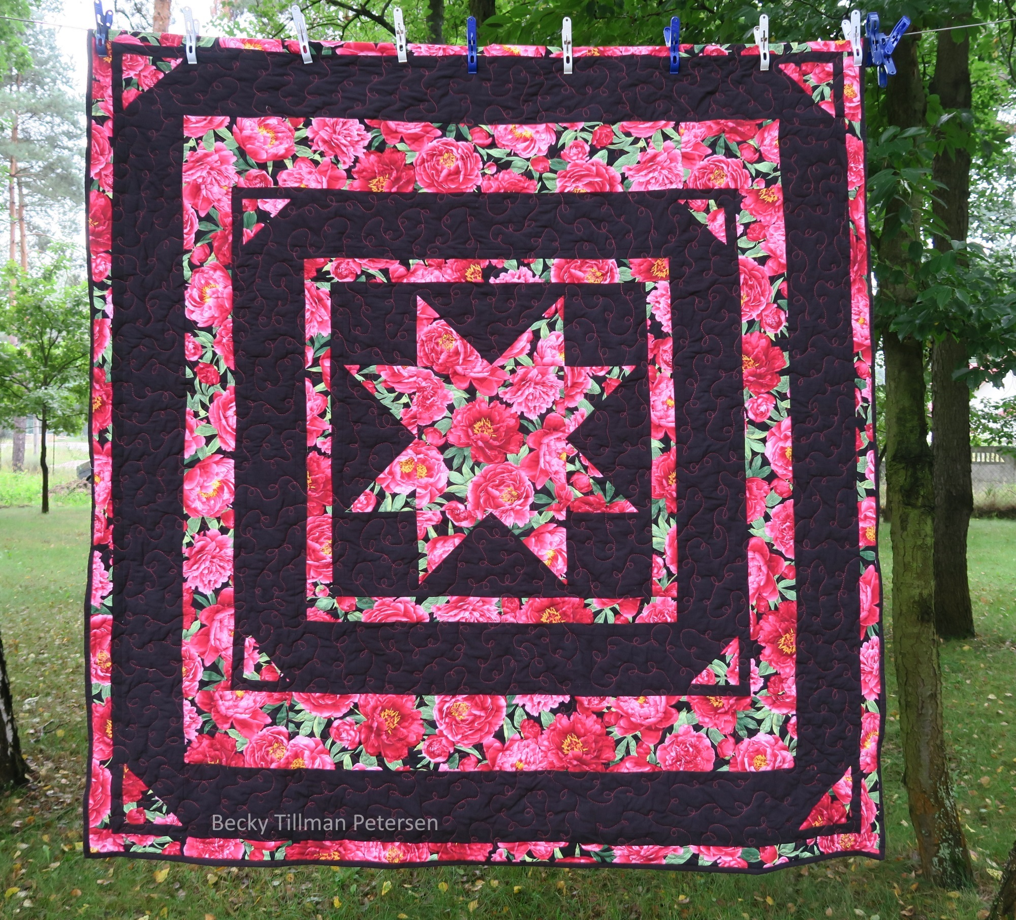 Big star quilt is completed and hung on a clothes line with trees in the background. Big star has rose and floral pattern in the star