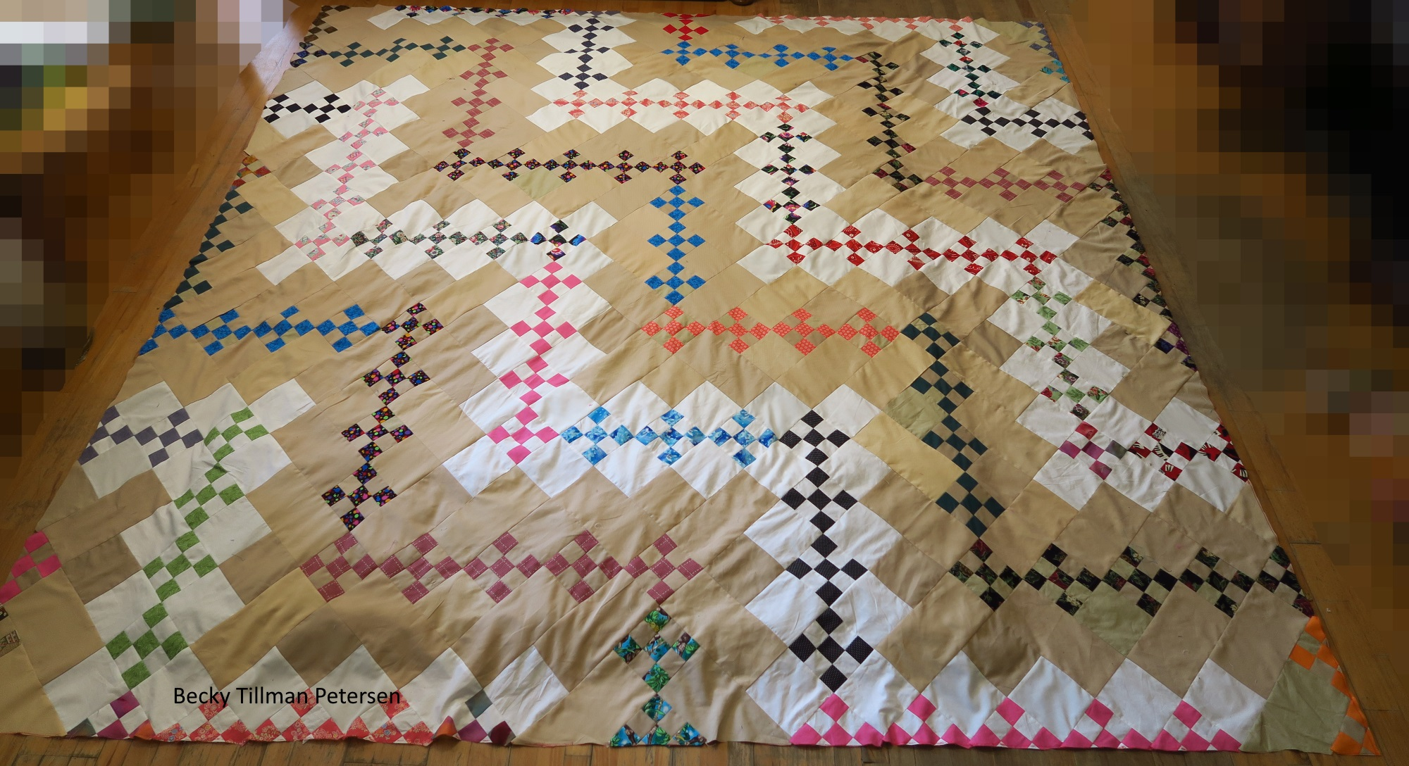 Zig-zag pattern quilt on wooden floor. Squares are arranged on quilt in a zig zag fashion four different times, giving the impression of lightning