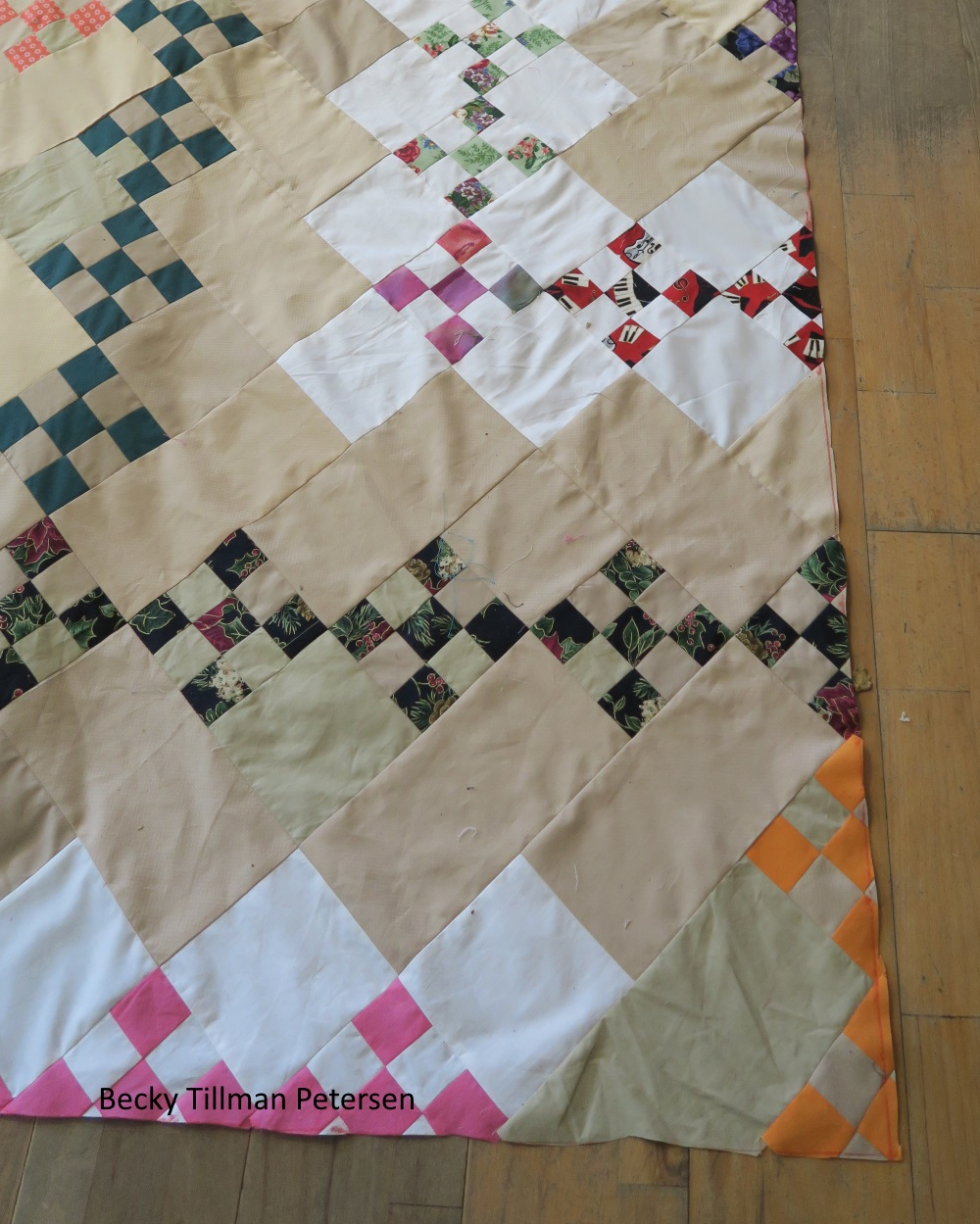 close up view of quilt: reveals that quilt is made up of small block composing the 2 inch squares. 5 small squares make are inside one of the zig zag patterns. One miniture block at each corner of the 2 inch fabric square, and one in the center (giving a checkered look).