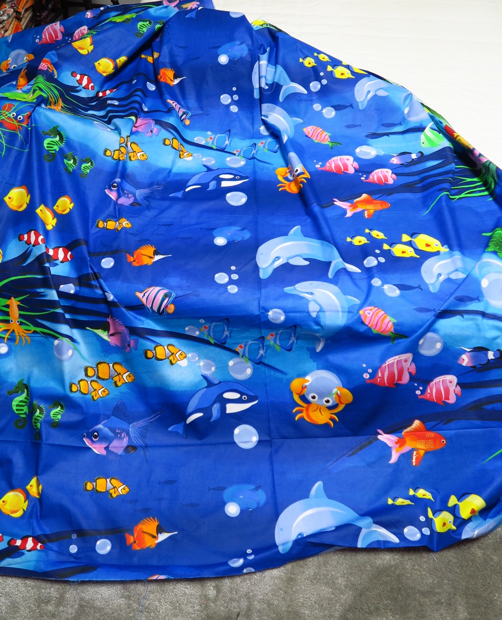 blue fabric with underwater sea design on it with a variety of fish and dolphins