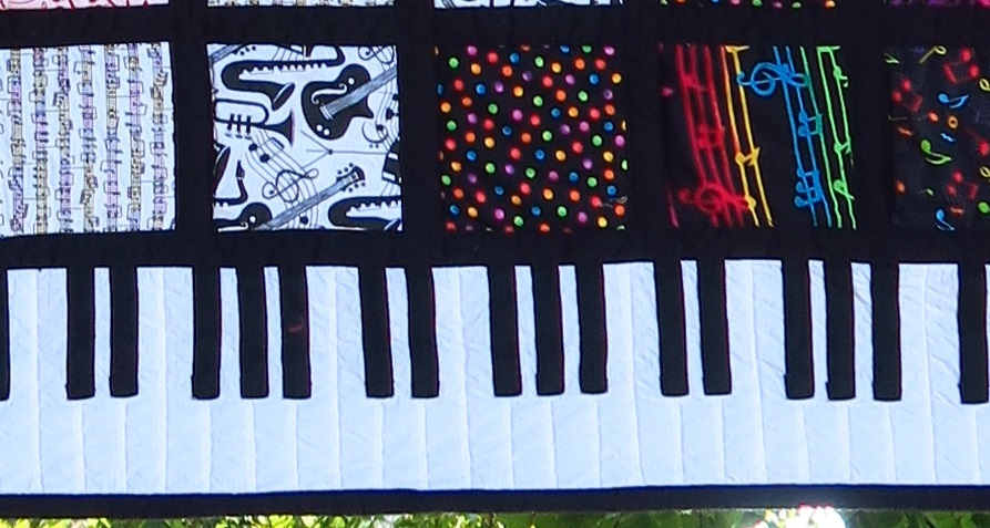 close up of piano key border, with black fringe on the bottom. Musical instruments, notes, and colors are in blocks above the border.