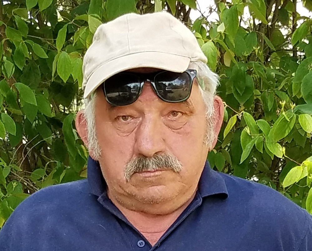 a male polish person with a white cap. His sunglasses are sitting on his forhead revealing is wide eyes. His snow hair is poking out below the cap, and his mustache has a little bit of dark to it. There is no visible expression of happiness that this man is conveying on his face.