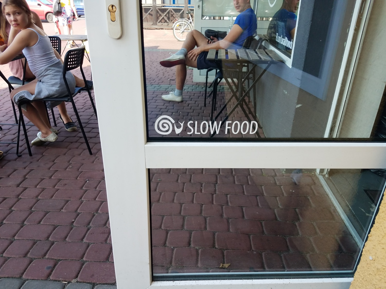 """""""slow food"""" writing on window of door of restaurent in poland."""