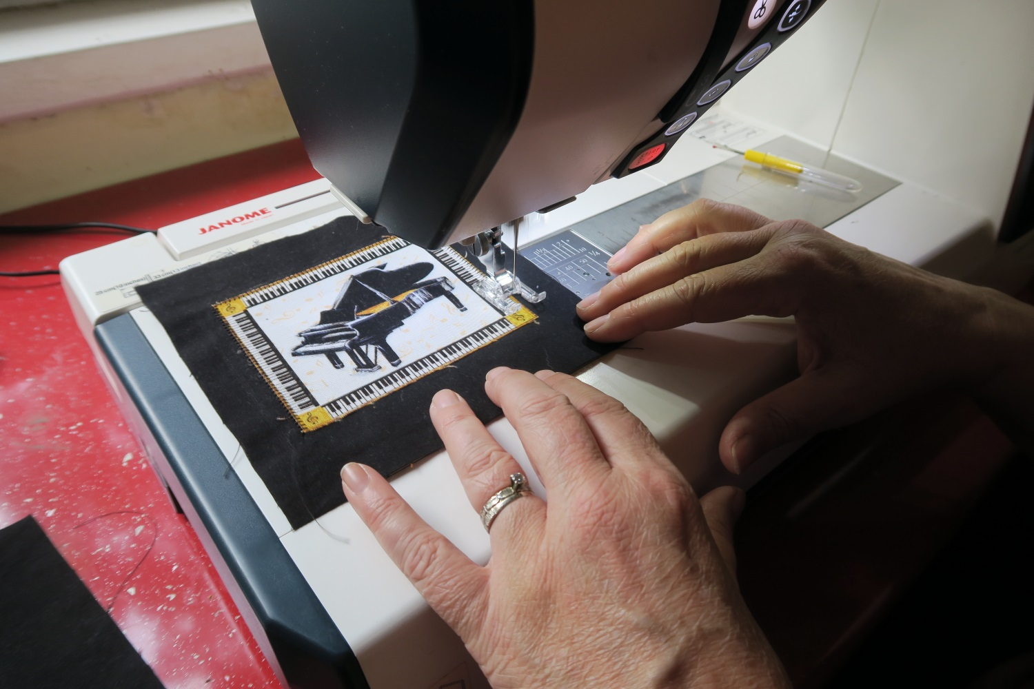 Musical patch of a piano is being sewn to the back of black fabric. The patch in and of itself has a piano keyboard around its border.