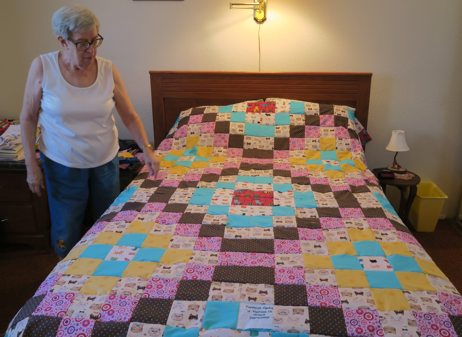 The big quilt top is made up of four smaller Around the World designs put together into one large top. It is draped over her guest bed to show me. She packs them in a box as she finishes them and then when the box is full, she ships it to me!