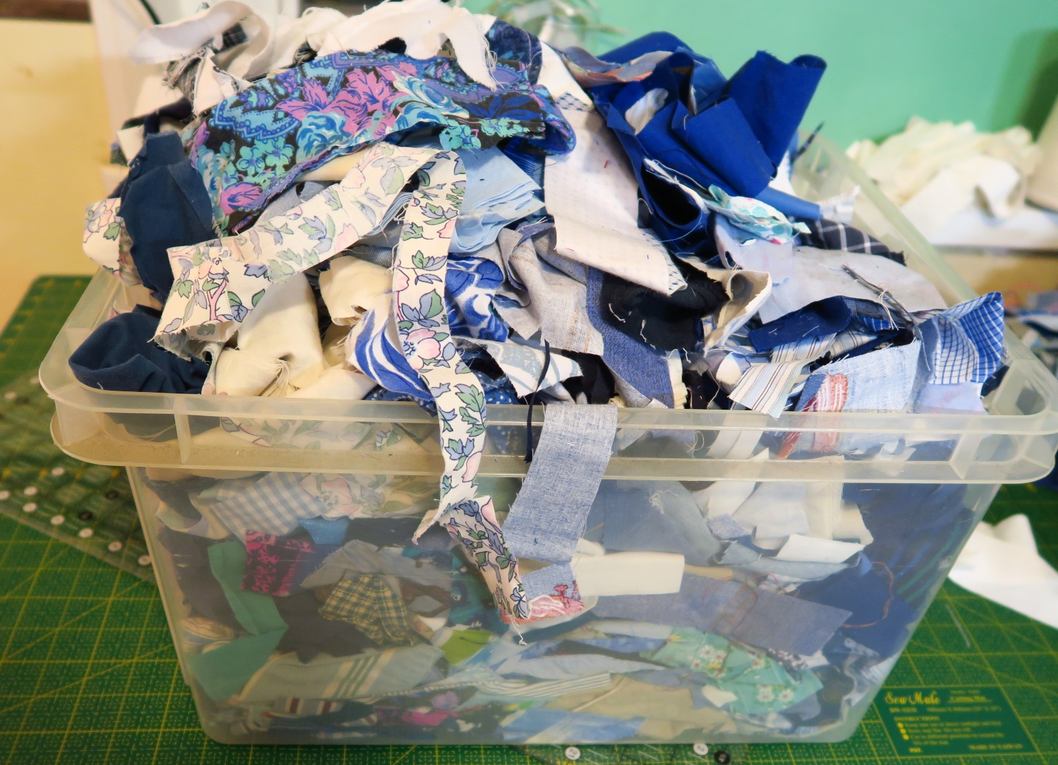 """I may have been a little too generous while throwing the scraps into this bucket. But I was trying to keep them corralled. I may go back through the bucket and actually cut out 2 1/2"""" squares from these scraps as I am using that size for the next quilt top."""