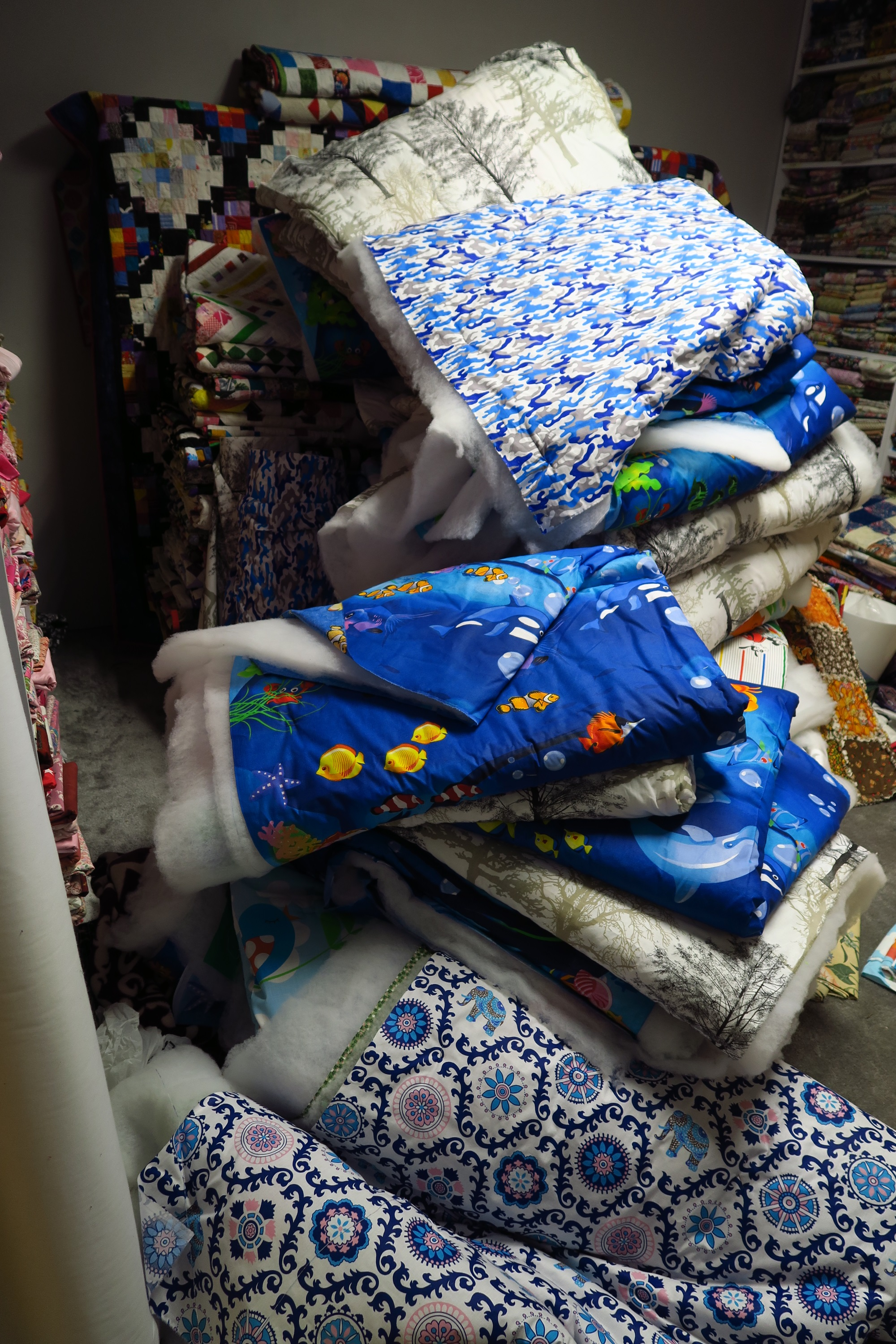 This is not a pile of 50 quilts.It's probably between 40 and 50, though. I have some in the sewing room right now and some were just outside the door of this room when I took the picture. You can pile sandwiched quilts only so high before they fall over.