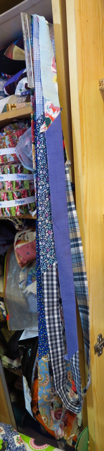 """Bindings in process. I have them hanging here on a ruler. I'll probably attach them to a hanger and let them hang up until the tops are quilted. I use 2.5"""" strips for this kind of binding."""