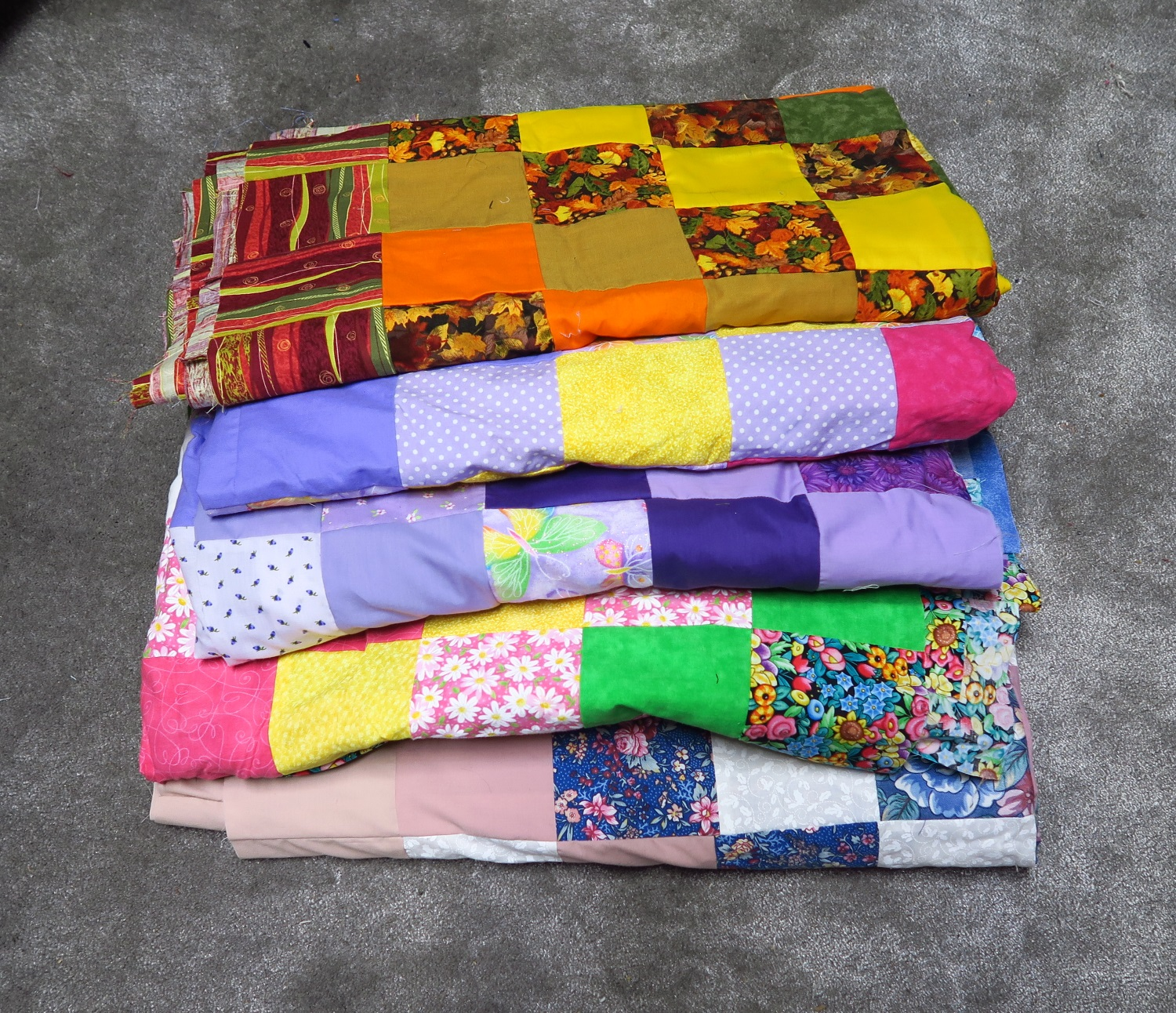 """My starter tops for the next group. I also have a collection of bigger panels (a couple) and several pillow panels that I can """"build on"""" to make some more tops. People like those a lot."""