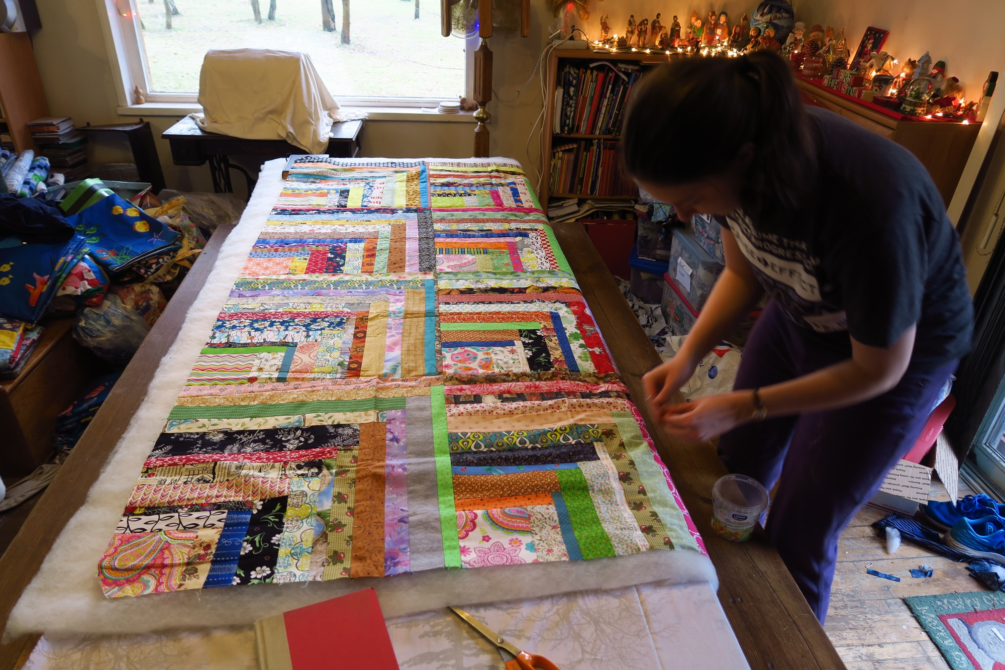 Sandwiching a beautiful donated quilt top!Lydia helped me sandwich almost half of the 120. We ran out of safety pins at 58. We did this mostly in early January before she headed back to college.