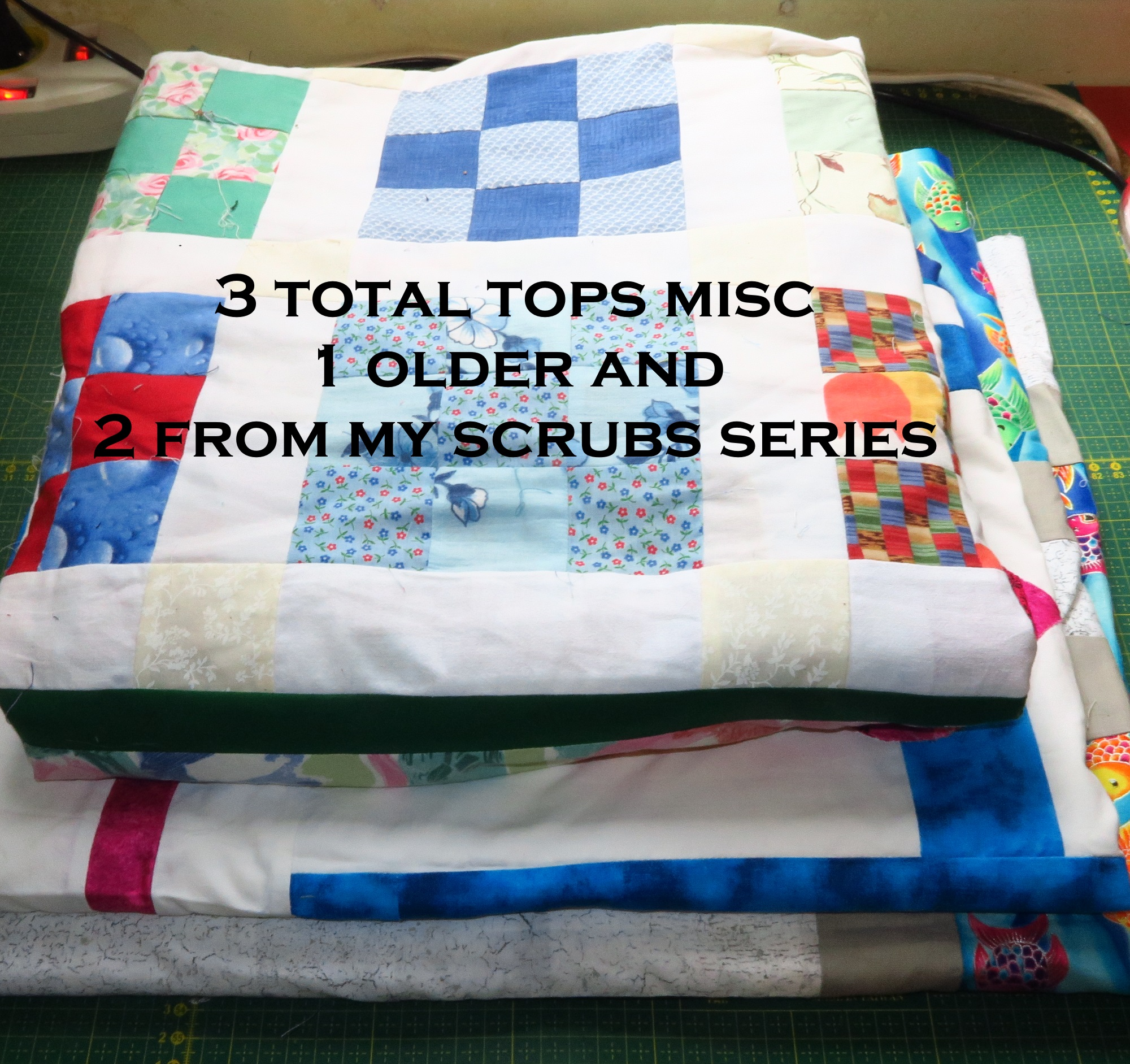 the top one is a simple 9 patch scrappy with a wide border - and the bottom two are from my scrubs fabrics series. 3 tops.