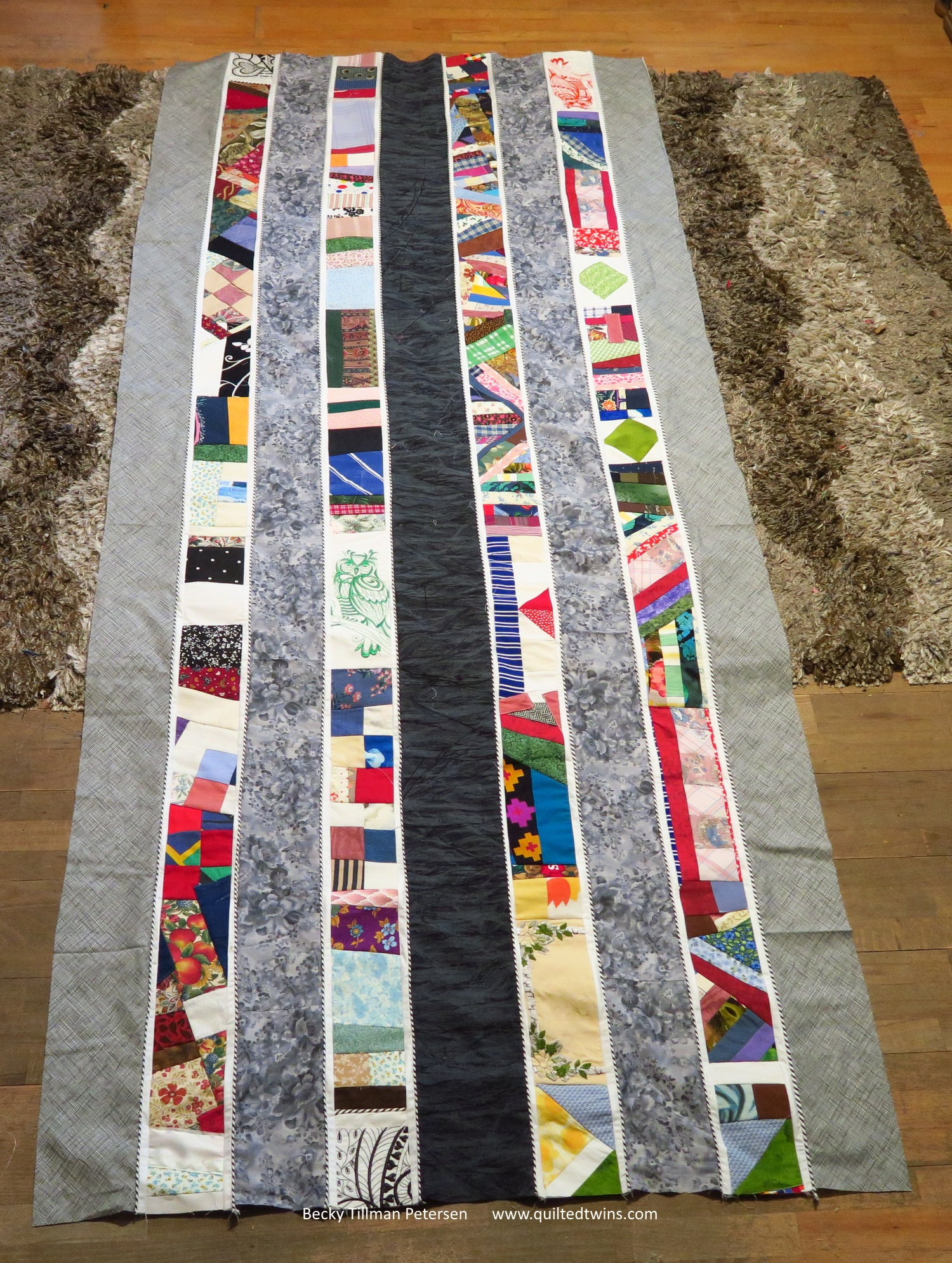"""This is all I've gotten done - it is about 40"""" wide and 96"""" long. I've been cutting things to the right length and pin and fit each piece - the white and the grays. I just sewed the piping on without measuring it first."""