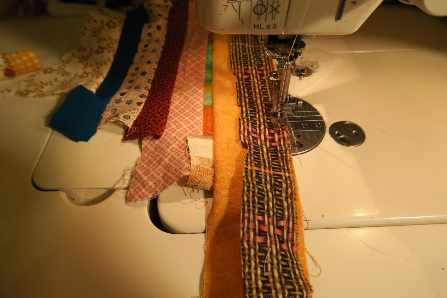 Open out the strings and pull tight as you sew the next strip on.