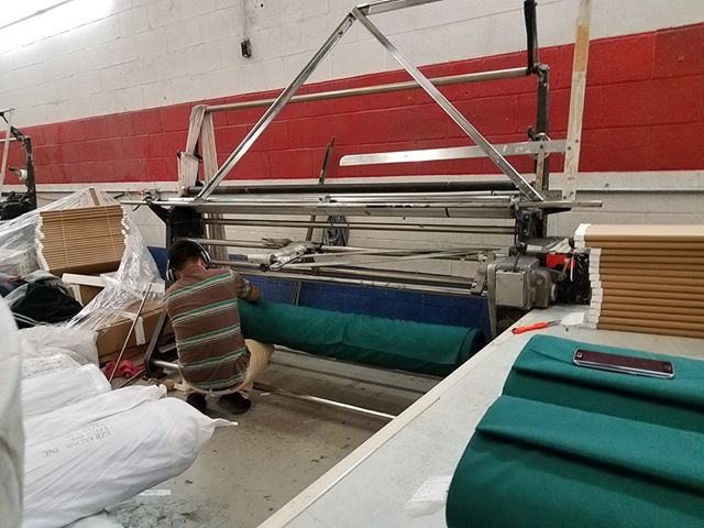 This is the machine that the big rolls are put on so that they can then unrolled from and put on to the small cardboard bolts. Here the guy is putting the roll on the bottom and starting to feed it through the rollers.