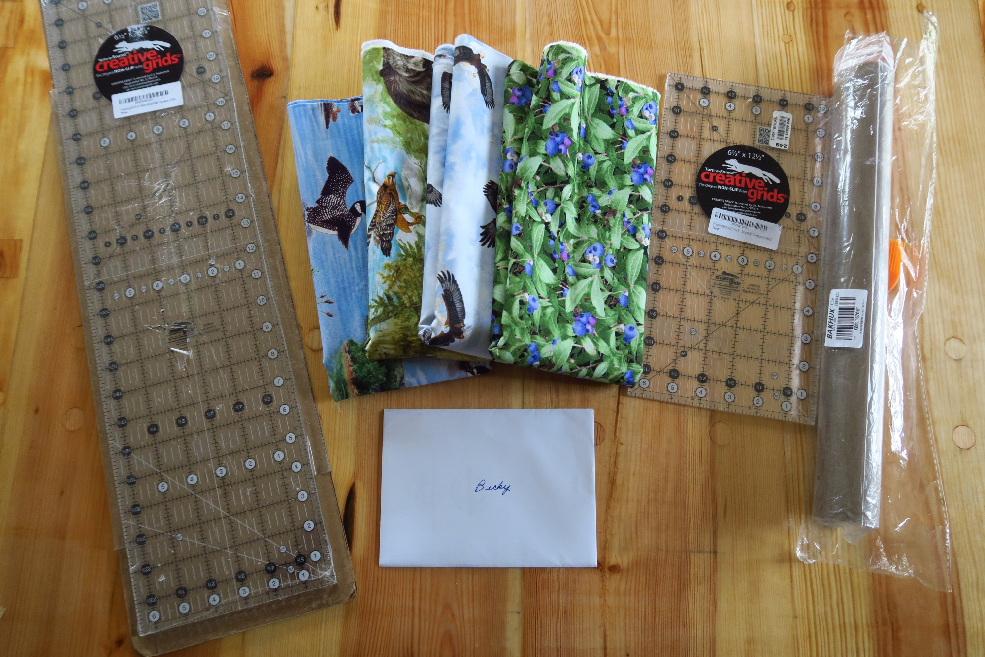 They include rulers, a thank you note from the couple who got the Alaska themed quilt, 4 pieces of fabric and some non stick baking sheets which I'm going to try instead of a Supreme Slider.
