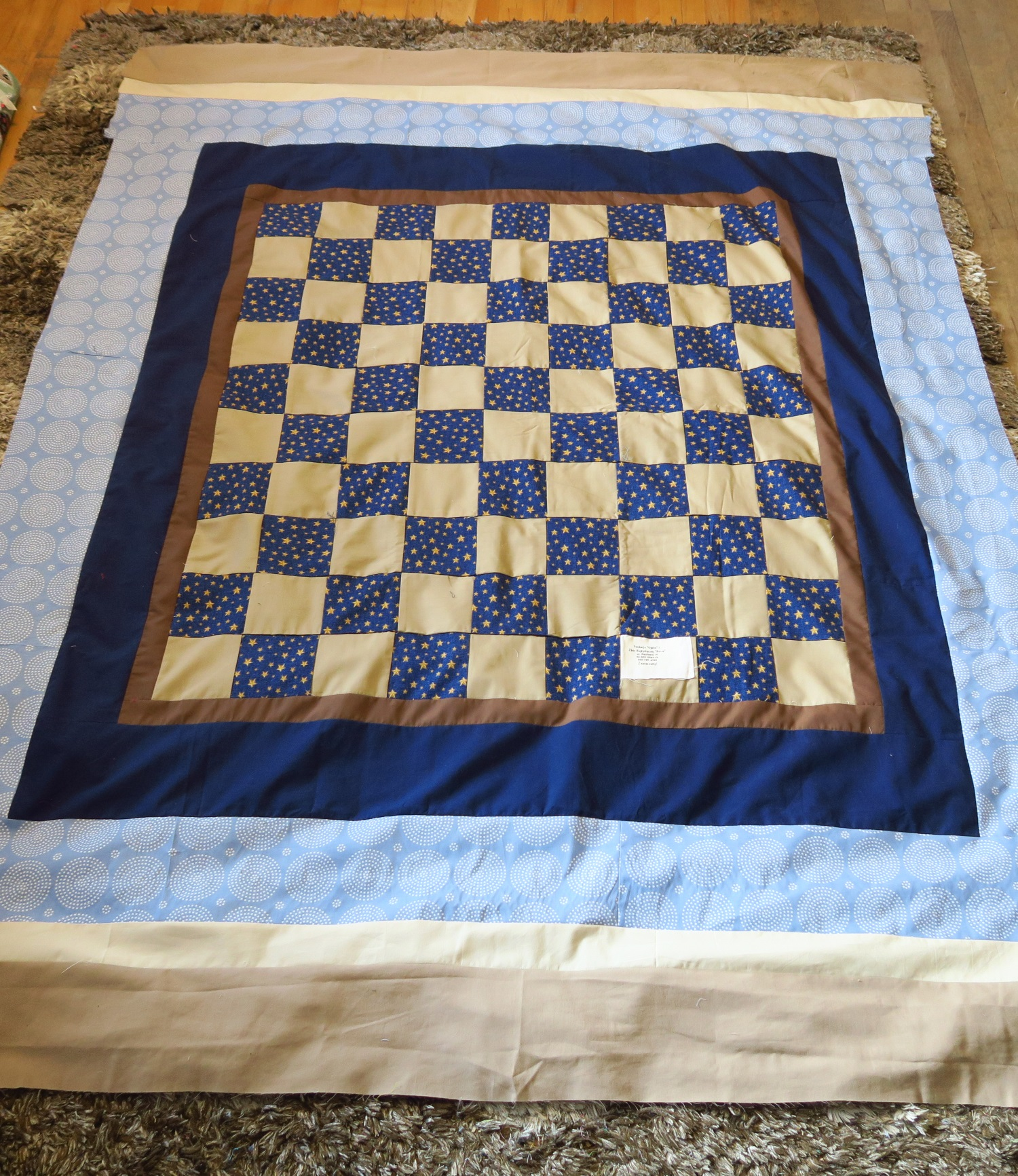 Here's the n avy blue and tan one shown above with the borders added. I didn't use her muslin backing as one of the borders. I'll save it and use it for something else.