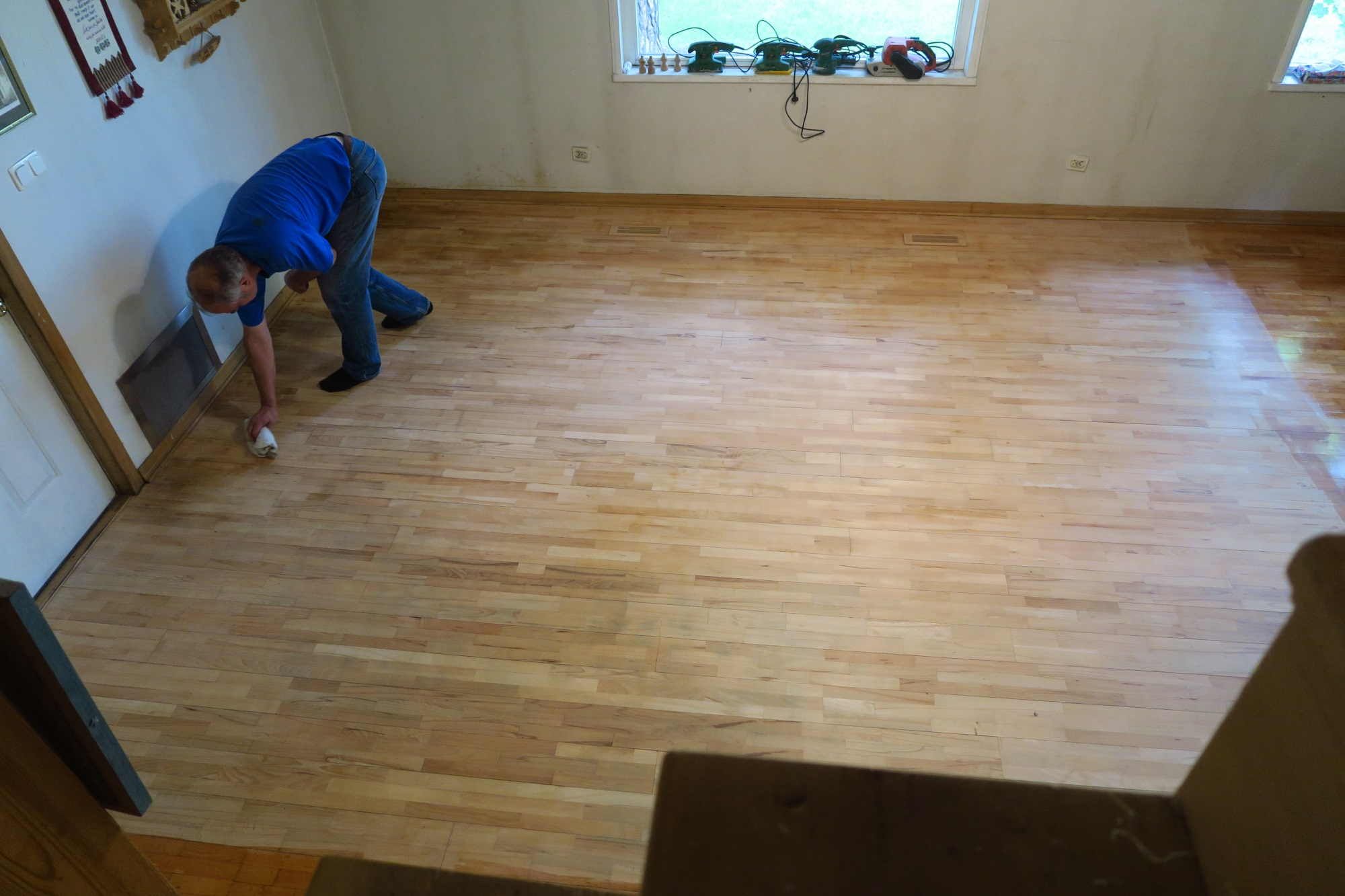 My husband is wiping down the floor before he varnishes the first time. He had sanded extensively - had the shop vac connected to the sander, so most of the sawdust was collected as he went along.