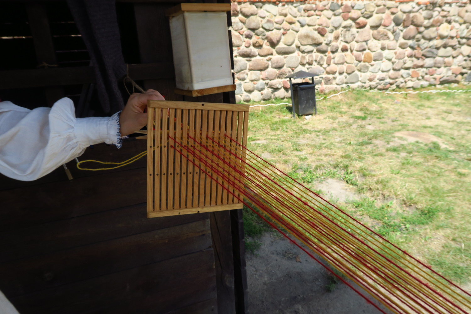 Weaving in a simple loom from the 1800s