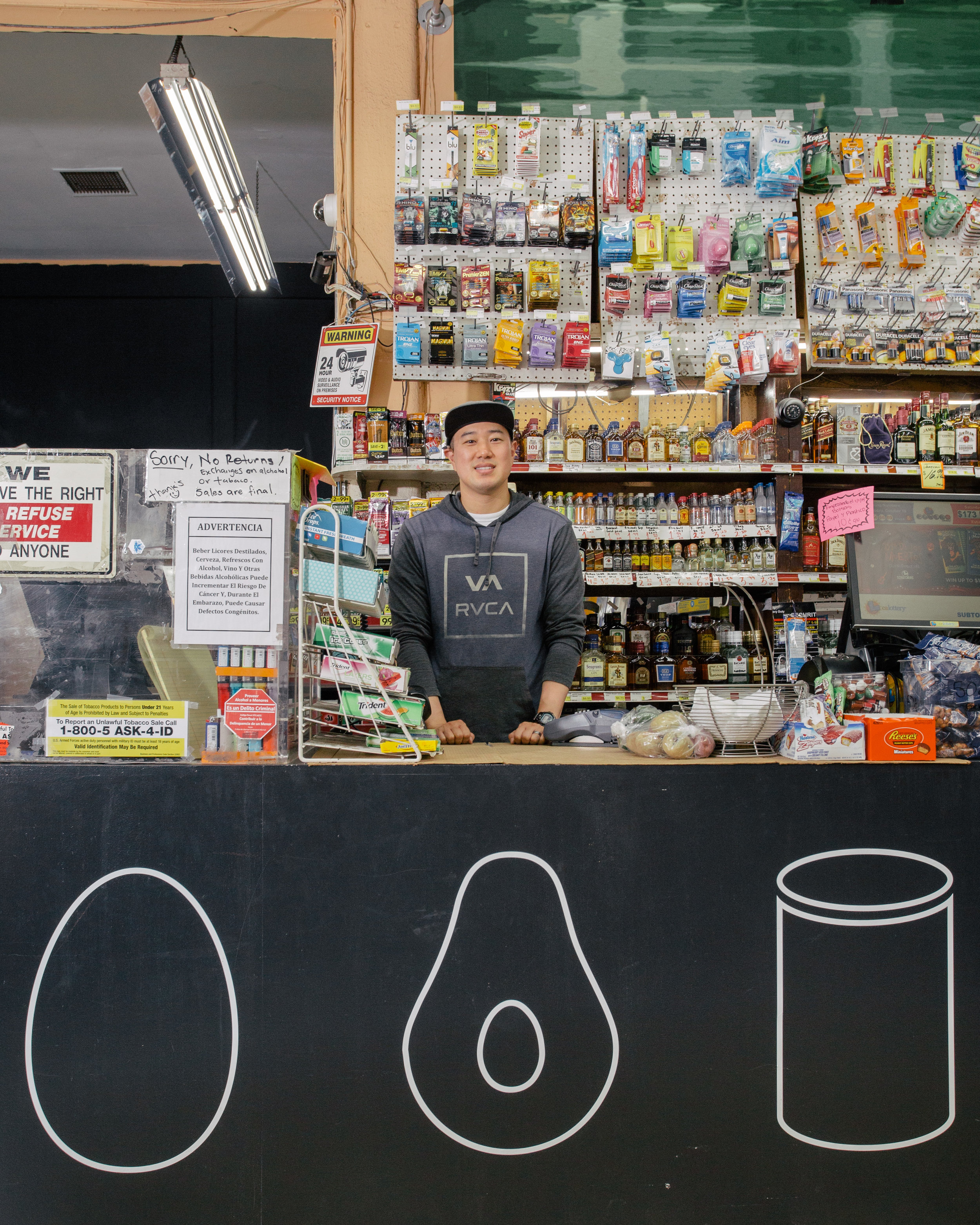 Andy Lee, owner of Sam's Corner Store, standing behind his new check-out counter, featuring healthy food icons. (This project was a part of the Healthy Neighborhood Market Network, in collaboration with the LA Food Policy Council.)