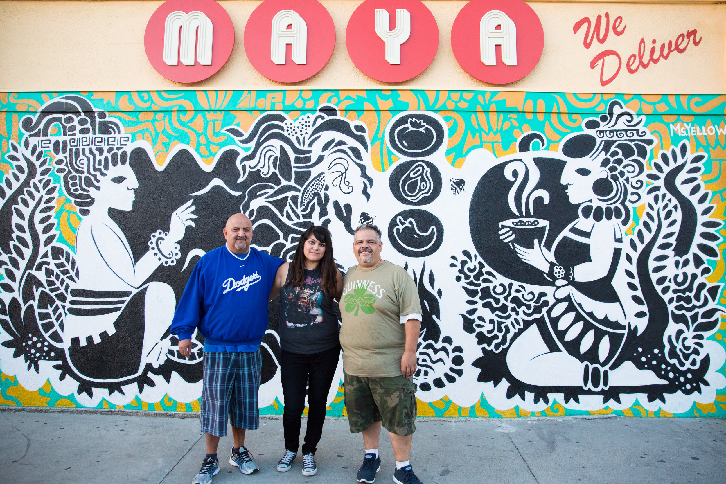 Maya Mexican Restaurant owners Rudy and Ricardo Sanchez, along with mural artist Nuria Ortiz (Ms. Yellow), in front of their new signage and mural in Wilmington, Los Angeles. (This project was part of the On Avalon: Small Business Support Program.)
