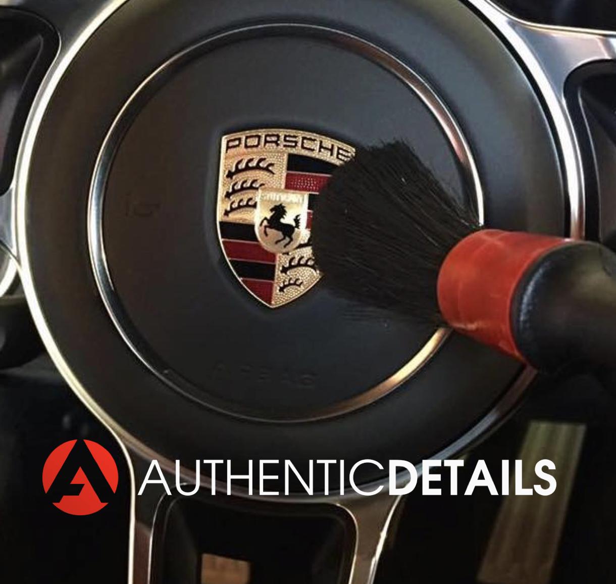 Fine brush on Porsche emblem to remove small dust particles