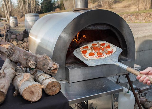 About to load up a meat lovers pizza in to one of our wood fired pizza ovens. The oven runs at about 900 degrees Fahrenheit so it'll be out in about two minutes. Yum!! 😋