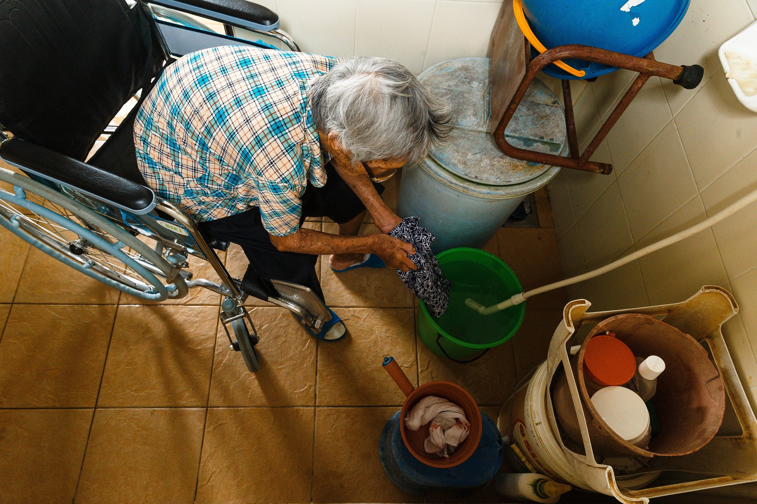 86 years old and rely on a wheelchair to move around, but she insists on washing her own clothes daily.(photo by Mango Loke)