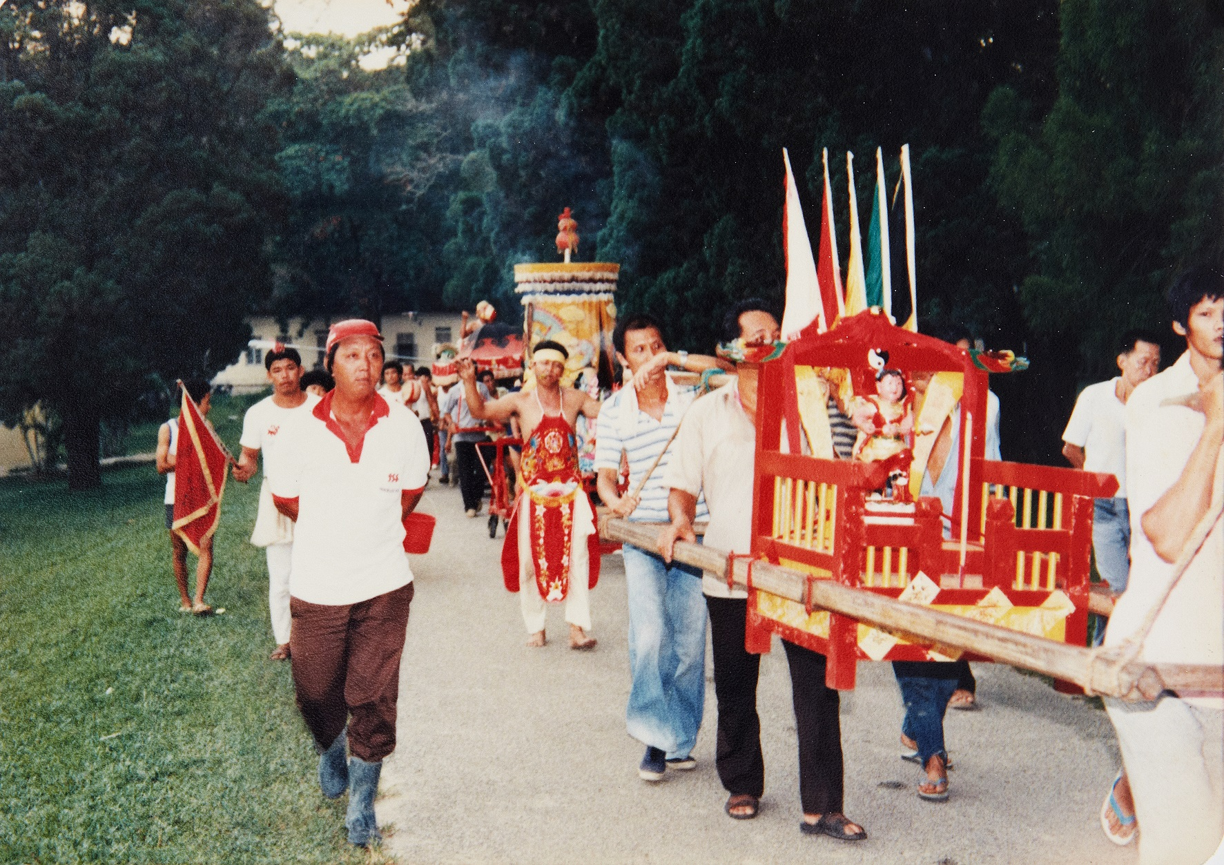 Taoist devotees carrying a palanquin during the procession to bless the people staying in the settlement. (photo courtesy of Fuh Huey Kong)