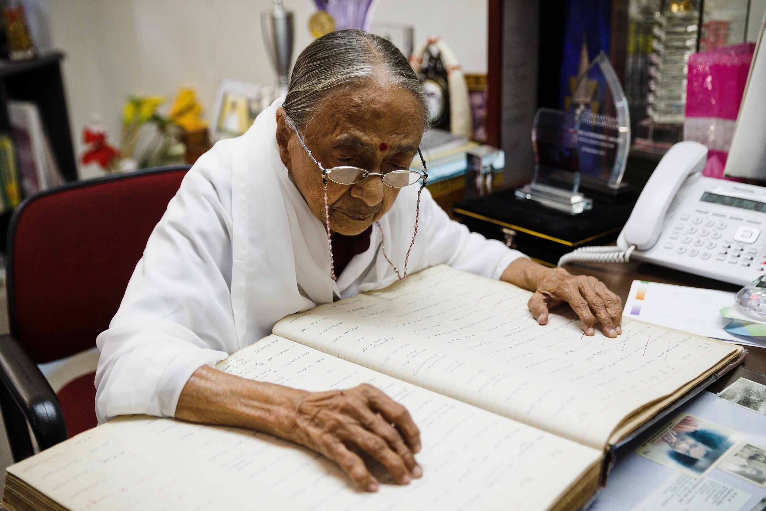 孟卡兰翻阅旧档案,查找来自双溪毛糯麻疯病院院民  子女  的资料。(陆奕萌 摄)