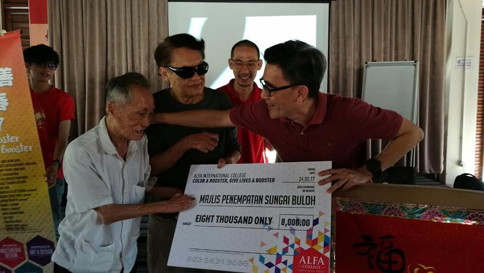 Alfa International College presenting mock cheque to the Sungai Buloh Settlement Council. (photo by Lim Mei Kim)