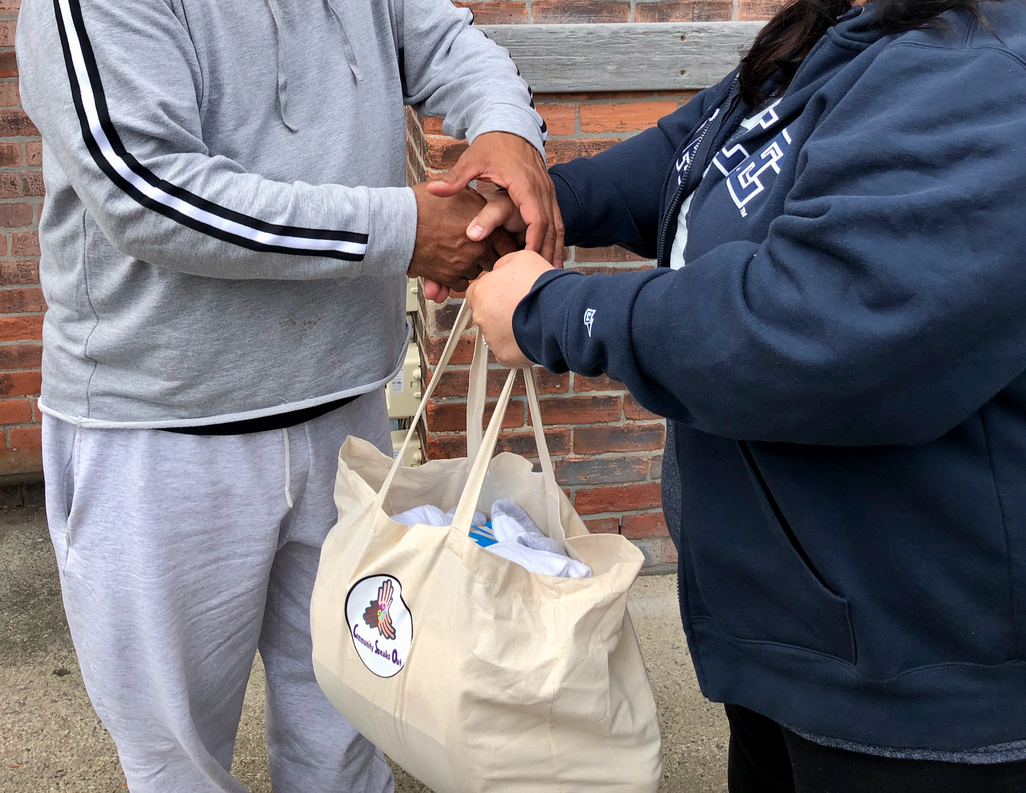 U.S. Army veteran in recovery receives a care-bag from Community Speaks Out volunteer.