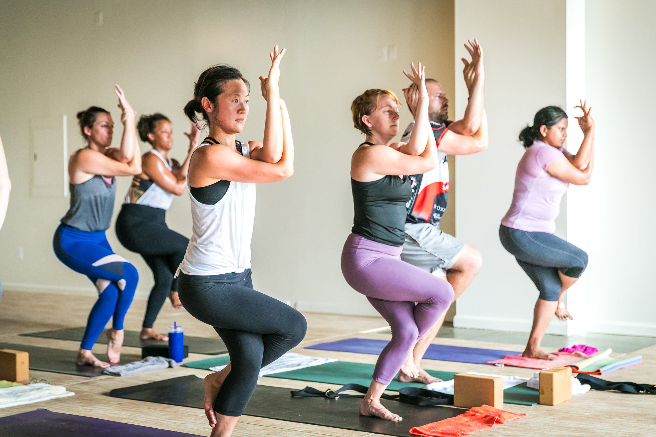 Heat yoga class students in Eagle pose