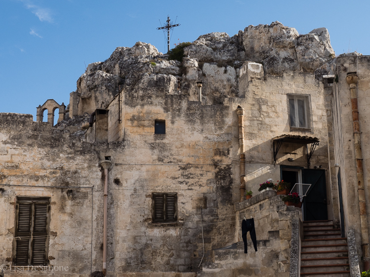 The uniqueness of Matera: on one side of the rock there's a church and on the other the day's laundry