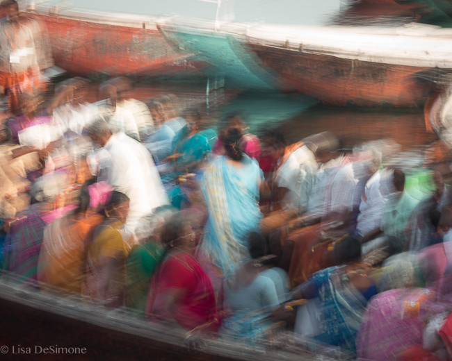 Locals taking a boat ride on the Ganges River in Varanasi, India.