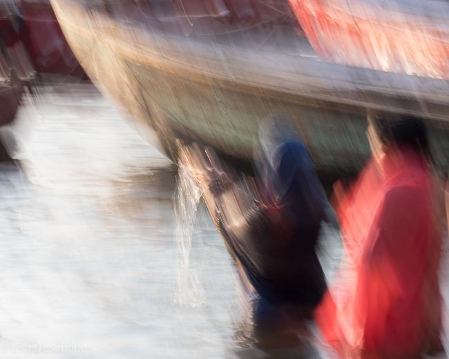 Two women in beautiful saris perform spiritual rituals in the Ganges River in Varanasi, India.