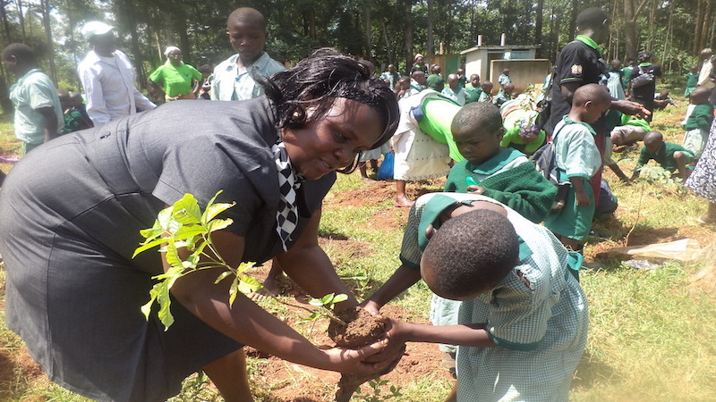 Violet Shivutse plants trees with students in Kenya (Photo: Huairou Commission)